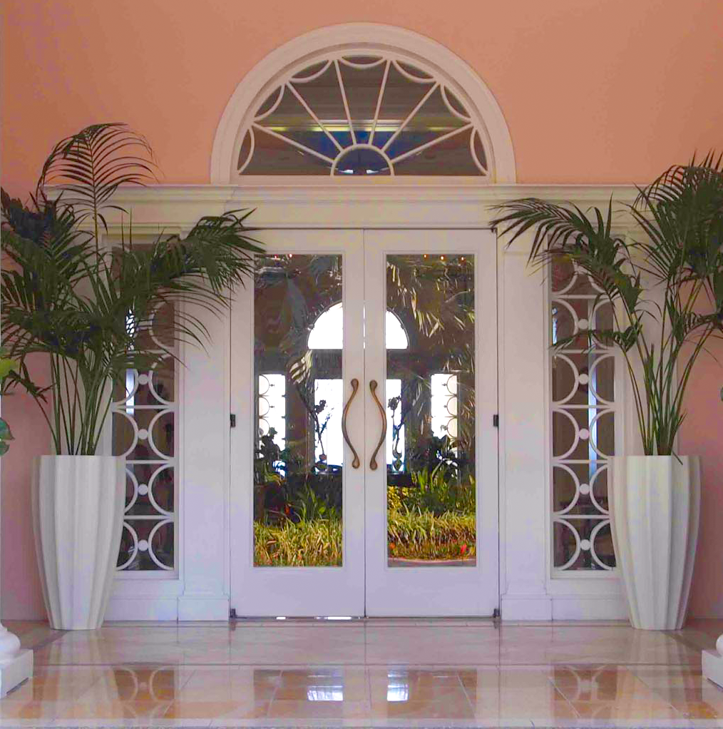 two white fluted planters with tall palms in a peach colored entryway