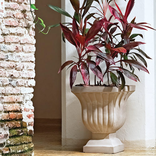 a white concrete-like fluted urn planter with a red plant sits next to a column and brick wall