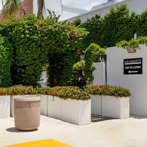 a series of white ribbed rectangle planter boxes line the exit to a patio walkway