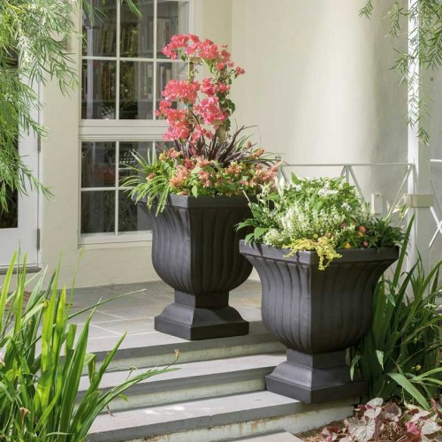 two black urn fluted planters with greenery and flowers ascending exterior stairs