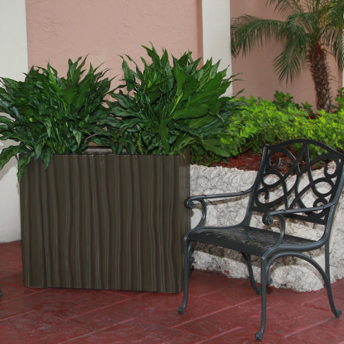 a brown rectangular fluted textured planter with greenery next to a black iron chair and white stone wall