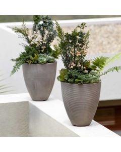 two slate grey textured resin planters with a greenery arrangement lined up on a ledge