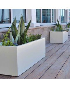 two white low profile planter boxes with greenery sit on a deck alongside the edge of a building