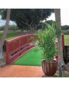 a golf course red bridge over a waterway is accented by two tall trees and a wide round fluted planter in brown with a palm tree