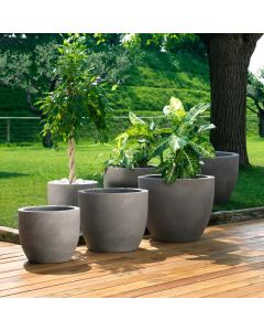 six round faux stone planter pots in ascending sizes sit on the edge of a wooden walkway and house greenery